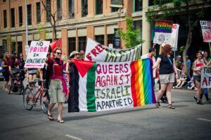 """Two people carry a banner in a Pride march which says """"Queers Against Israeli Apartheid"""" and which has on one side the flag of Palestine and on the othernd the rainbow flag. Behind them another banner reads """"Free Palestine"""""""