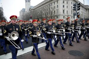A line of trombonists leads a large military band in full regalia down a wide city street