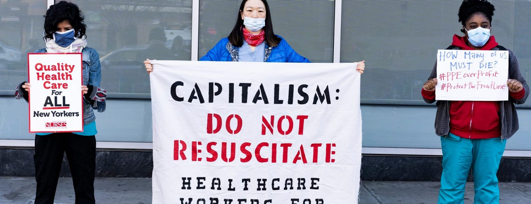 Healthcare workers in masks hold up three protest signs and banners: Quality Health Care for All New Yorkers, Captialism: Do Not Resucitate: Healthcare Workers for Socialism, How Many of us must die? #PPEoverprofit #ProtecttheFrontLine