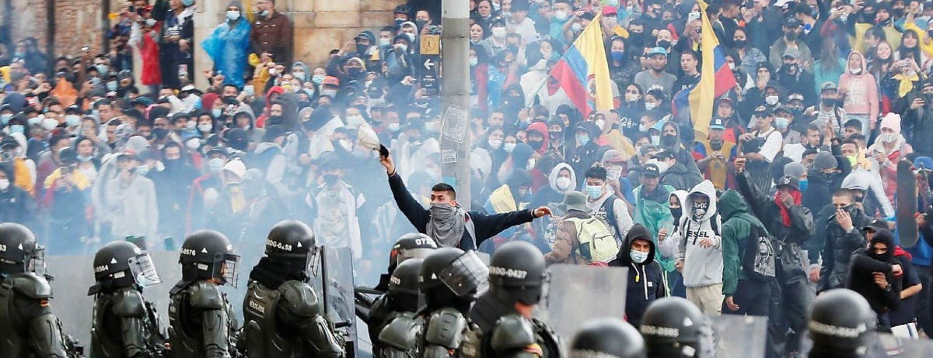 Colombian protesters advance through tear gas towards a police lline