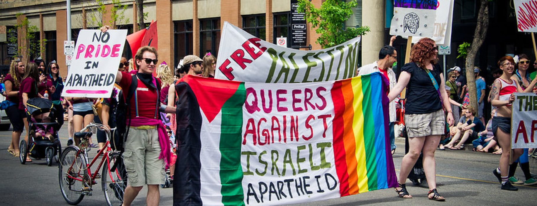 Two people carry a banner in a Pride march which says