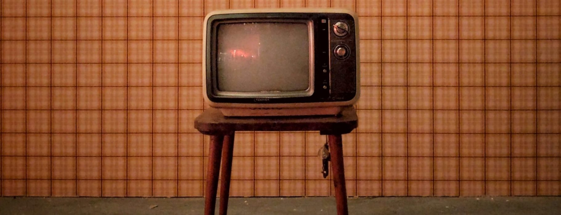 Vintage television set against a checked wallpaper background