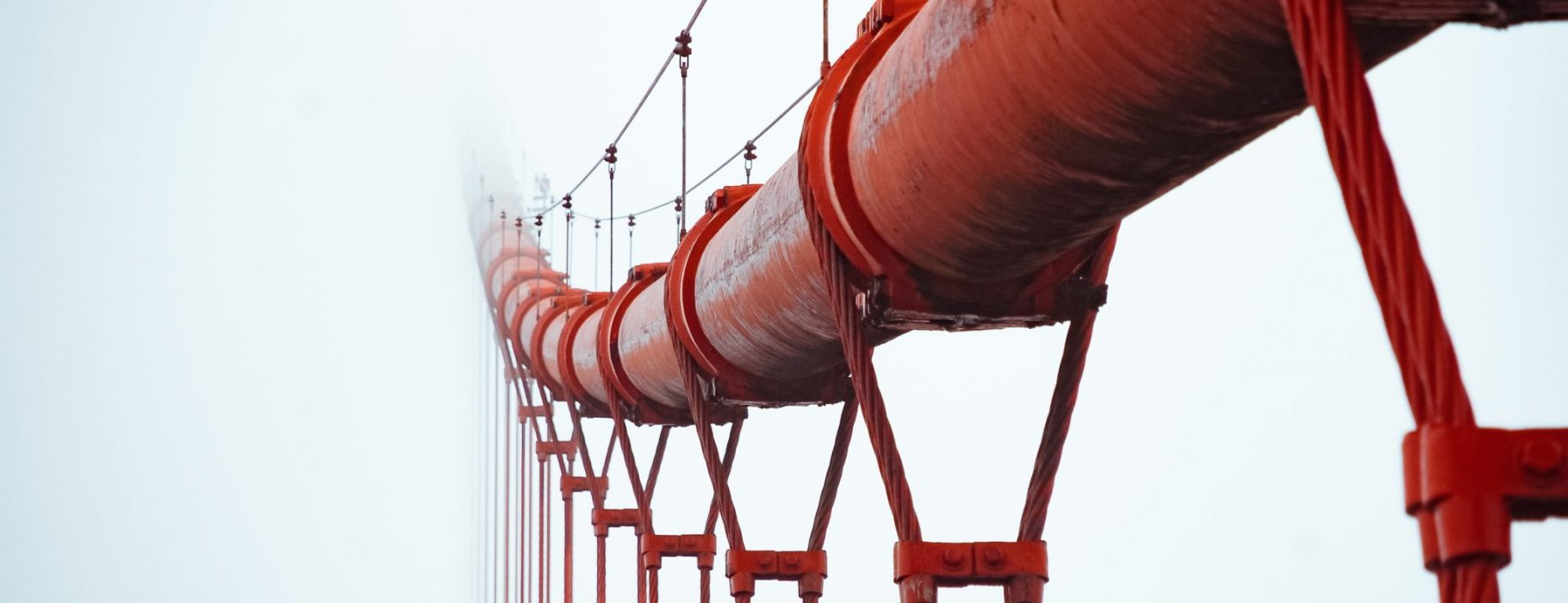 A red pipeline, upheld by a bridge of metal cables, fades into the white mist. Photo by JJ Ying on Unsplash
