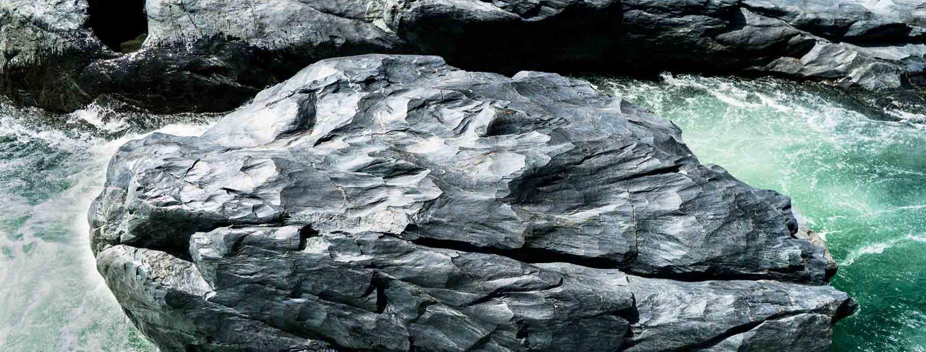 A river flows around a boulder